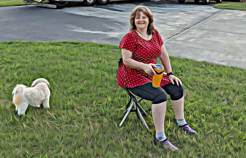 Denise sitting in easy to carry three legged stool with back